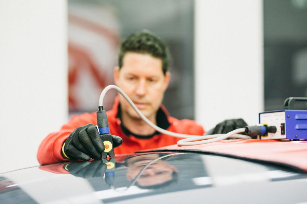 Un tecnico tirabolli mentre applica l'induzione su un veicolo con ammaccature da grandine